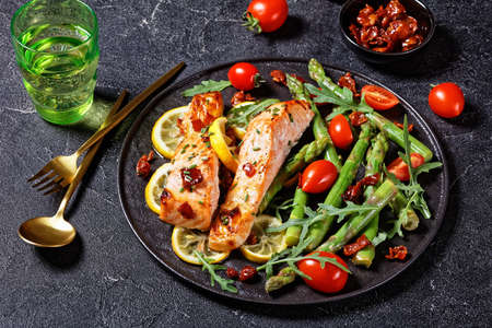 baked salmon with lemon and caramelized bacon served with asparagus cherry tomatoes wild rocket salad on a black plate with golden cutlery