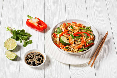 Shrimp Pad Thai with vegetables, tamarind sauce, spring onion and herbs in a white bowl on a wooden table, thai cuisine 写真素材
