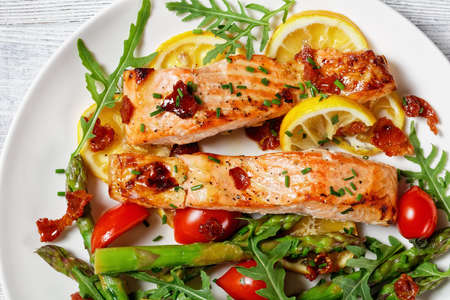 grilled salmon fillets with lemon and caramelized bacon served with asparagus, cherry tomatoes, wild rocket salad on a white plate 写真素材