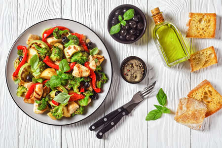 Vegetable roast: broccoli and chicken with young potato, pepper, courgette, olives, sprinkled with balsamic vinegar and basil on top, served on a plate on white wooden background, top view, close-up 写真素材