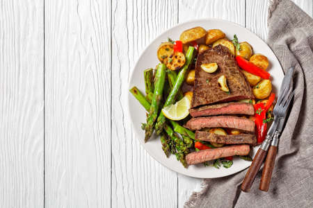 beef steak with barbequed new baby potatoes, asparagus, lemon and red pepper on a white plate with barbecue sauce on a wooden table, flat lay, free space 写真素材