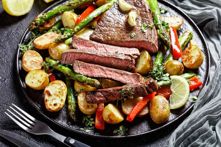 close-up of beef steak with roasted vegetables new baby potatoes, asparagus and red pepper on a black plate 写真素材