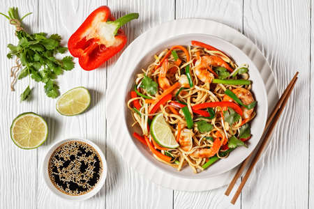 Shrimp Pad Thai with vegetables, tamarind sauce, spring onion and herbs in a white bowl on a wooden table, flat lay,  thai cuisine 写真素材