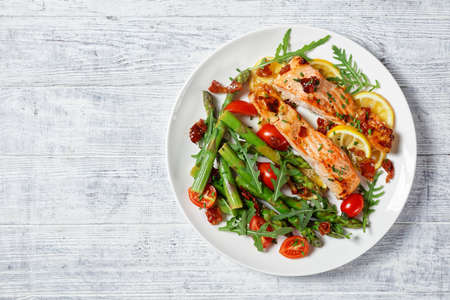 baked salmon fillets with lemon and caramelized bacon served with asparagus, cherry tomatoes, wild rocket salad on a white plate, flat lay, free space