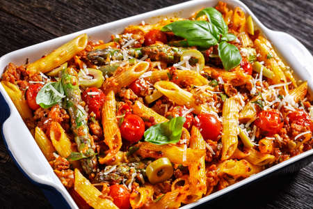close-up of ground turkey penne pasta bake with asparagus, tomatoes and olives in a baking dish on a dark wooden table, italian cuisine 写真素材