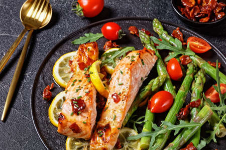 close-up of baked salmon with lemon and caramelized bacon served with asparagus cherry tomatoes wild rocket salad on a black plate with golden cutlery on a concrete table 写真素材