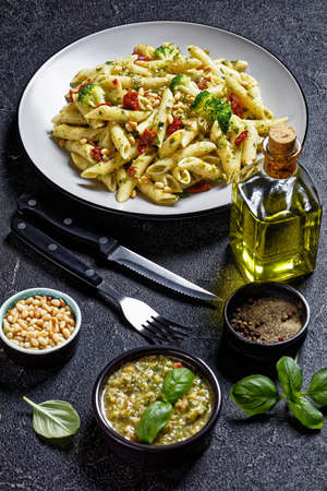 Broccoli pesto pasta with sundried tomatoes and pine nuts on a plate and ingredients on a concrete table, vertical view from above
