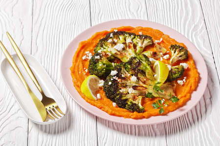 roasted broccoli steak with pumpkin mash topped  with crumbled feta cheese on a white plate, vegetarian recipe