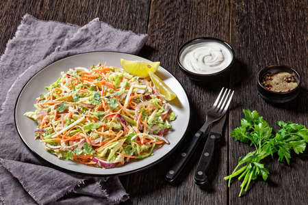 juicy low calorie coleslaw salad of cabbage, carrots, spring and red onions and parsley with light yogurt dressing on a plate on a dark wooden table with fork and knife