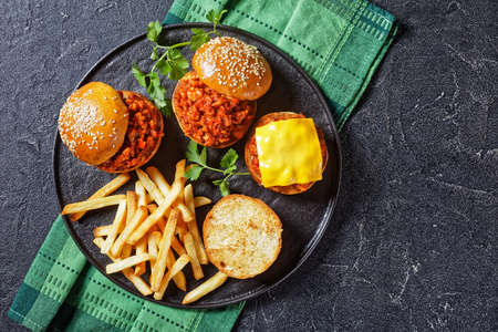 homemade BBQ Sloppy Joe sandwiches with french Fries on a black plate, flat lay, free space 写真素材