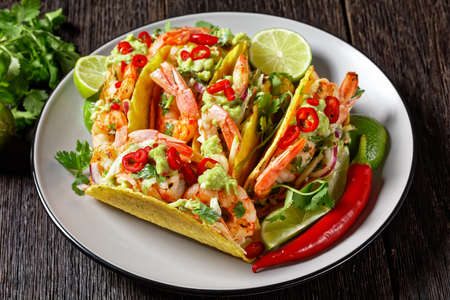 taco shells with grilled shrimps, cabbage salad, lime and guacamole on a plate