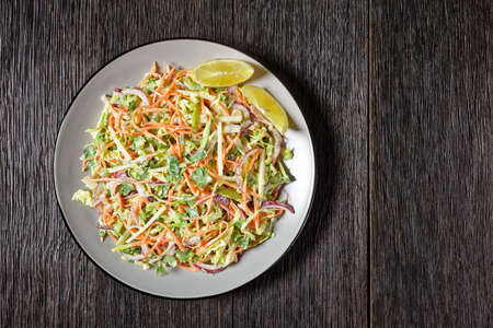 juicy low calorie coleslaw salad of cabbage, carrots, spring and red onions and parsley with light yogurt dressing on a plate on a dark wooden table, flat lay, free space 写真素材