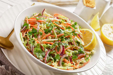 fresh summer coleslaw salad with light yogurt dressing in a white bowl on a textured wooden table, close-up
