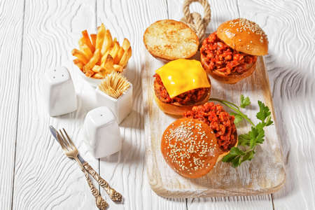 Sloppy Joe sandwiches on brioche buns served with french Fries on a white wooden board, close-up, american cuisine 写真素材