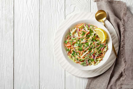fresh summer coleslaw salad with light yogurt dressing in a white bowl on a wooden table, flat lay, free space 写真素材