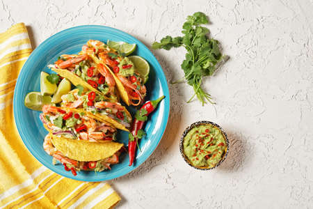 taco shells with grilled shrimps, cabbage salad, lime and guacamole on a blue plate on a white table, flat lay, free space