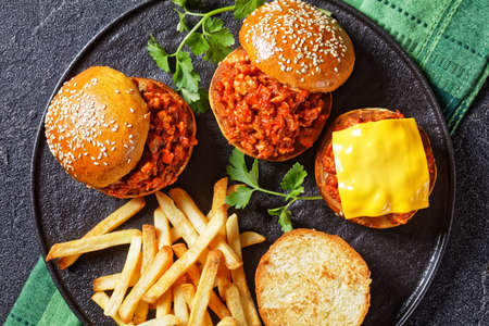 homemade BBQ Sloppy Joe sandwiches with french Fries on a black plate, flat lay, close-up, american cuisine 写真素材