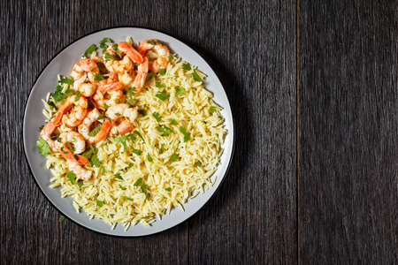 Lime shrimps with cilantro and long grain rice cooked with chicken broth served on a plate on a dark wooden background, copy space top view, close-up 写真素材