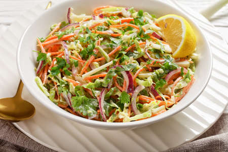 fresh summer coleslaw salad with light yogurt dressing in a white bowl on a wooden table,  close-up