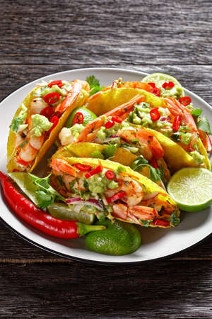 taco shells with grilled shrimps, cabbage salad, lime and guacamole on a plate on a wooden table 写真素材