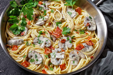 Italian pasta with cremini mushroom sauce of heavy cream and parmesan  cheese with crispy bacon and fresh parsley served on a metal skillet on a dark concrete background, top view, close-up