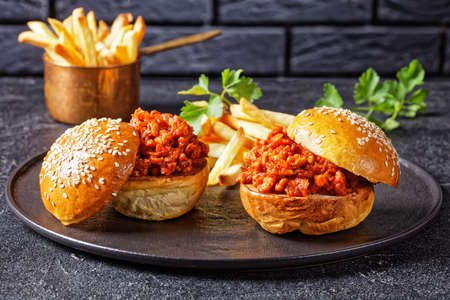 Sloppy Joe sandwiches with french Fries on a black plate with a brick wall at the background, close-up, american cuisine 写真素材