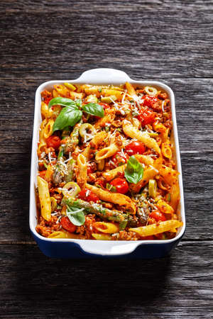 ground turkey penne pasta bake with asparagus, tomatoes and olives in a baking dish on a dark wooden table, vertical view, italian cuisine