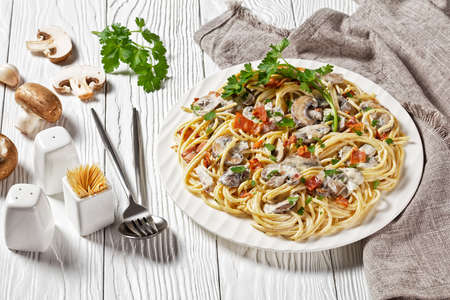 Italian spaghetti with cremini mushroom sauce of heavy cream and parmesan cheese with crispy bacon and parsley served on a white plate and cutlery on a white wooden background, top view, close-up