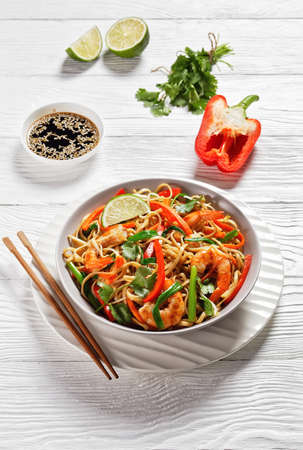 Prawn Pad Thai with vegetables, tamarind sauce, spring onion and herbs in a white bowl on a wooden table, vertical view, thai cuisine 写真素材