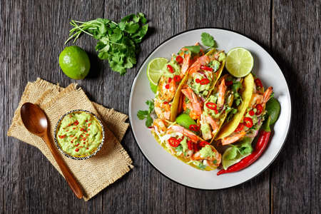 grilled shrimp tacos with cabbage salad, lime and guacamole filling on a plate on a wooden table, flat lay 写真素材