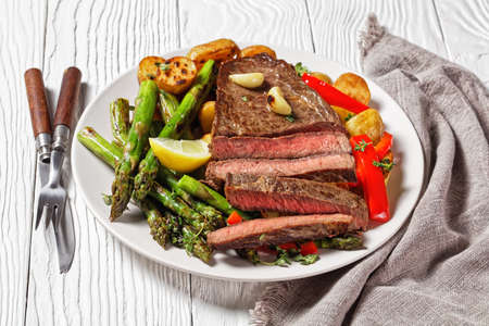 beef steak with barbequed new baby potatoes, asparagus, lemon and red pepper on a white plate with barbecue sauce on a wooden table