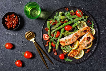 grilled salmon fillets with lemon and caramelized bacon served with asparagus cherry tomatoes wild rocket salad on a black plate with golden cutlery, flat lay