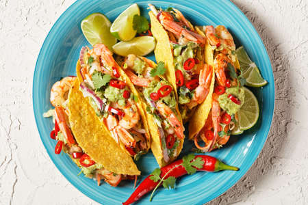 taco shells with grilled prawns, cabbage salad, lime and guacamole on a blue plate on a white table, flat lay, free space, close-up 写真素材