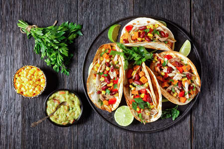 tacos of flour tortilla shells filling with grilled chicken meat, corn, roasted sweet potatoes cubes, red pepper and parsley served on a black plate