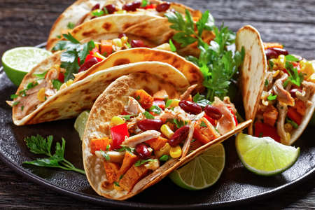 tacos of flour tortilla shells filling with grilled chicken meat, corn, roasted sweet potatoes cubes, red pepper and parsley served on a black plate, close-up 写真素材