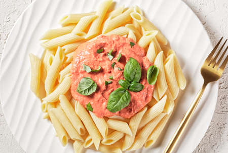 Pink Sauce Pasta, Parma Rosa Sauce with Penne on a plate with golden fork, flat lay 写真素材