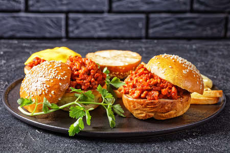 BBQ Sloppy Joe sandwiches with french Fries on a black plate with a brick wall at the background, close-up, american cuisine