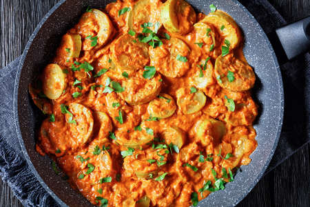zucchini braised in a creamy tomato sauce in a pan, italian cuisine, flat lay, close-up