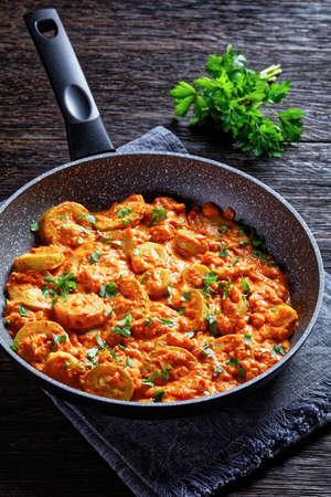 zucchini, summer squash in a creamy tomato sauce in a pan, italian cuisine, vertical view