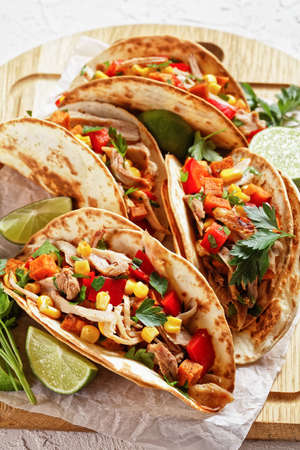 tacos with grilled chicken meat, corn, roasted sweet potatoes cubes, red pepper  and parsley served on a wooden board on  a white concrete table