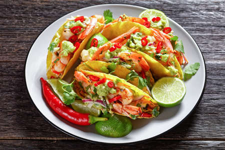 shrimp tacos with fresh cabbage salad, lime, chili and guacamole on a plate