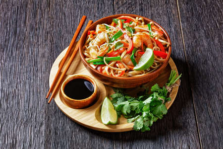 pad thai noodles stir-fry with prawns, carrots, red pepper, coriander and lime wedges in a bowl on a bamboo tray with soy sauce and chopsticks