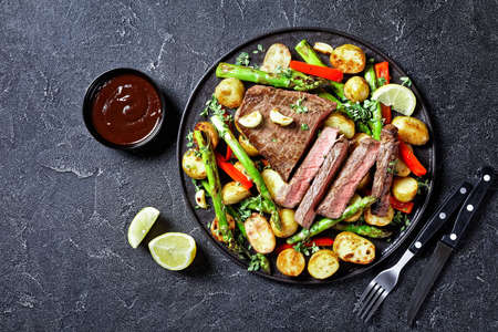 beef steak with roasted new baby potatoes, asparagus and red pepper on a black plate with barbecue sauce on a concrete table, flat lay, free space
