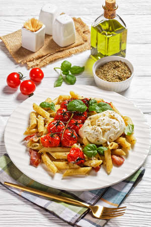 Vibrant italian pasta bake of penne, bacon, cherry tomatoes, and mozzarella cheese, parmesan, fresh basil served on a white plate with fork and ingredients on a white wooden background, close-up