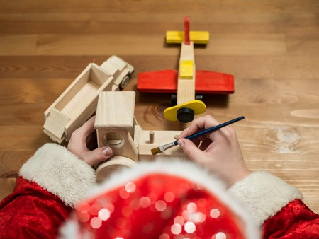 toy plane: Santa Claus sitting in his workshop painting a toy airplane. Horizontal composition.