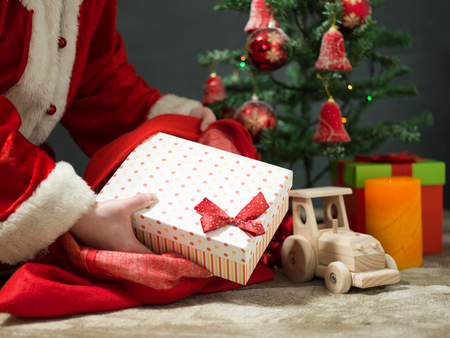 saint nick: holidays, celebration and people concept - close up of santa claus putting present under christmas tree