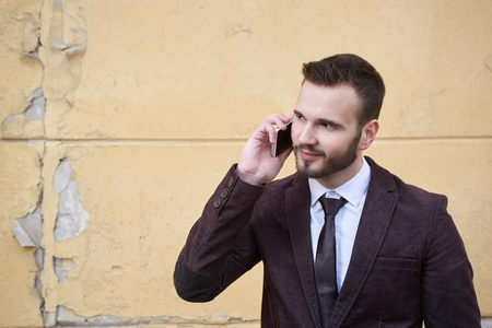 suave: Smiling businessman standing outside office building and talking on the phone