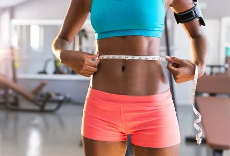 loosing: Gym afro woman loosing weight and taking measurements Stock Photo