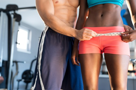 Conceptual photo of beautiful young afro american woman measuring her body with professional trainer. Stock Photo