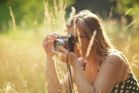 Young female photographer holding a vintage camera. Stock Photo